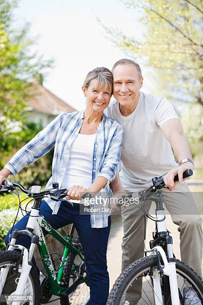 Portrait of smiling senior couple on bicycles