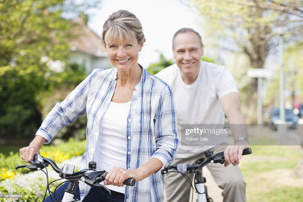 Retrato de sorrindo casal de idosos em bicicletas : Foto de stock