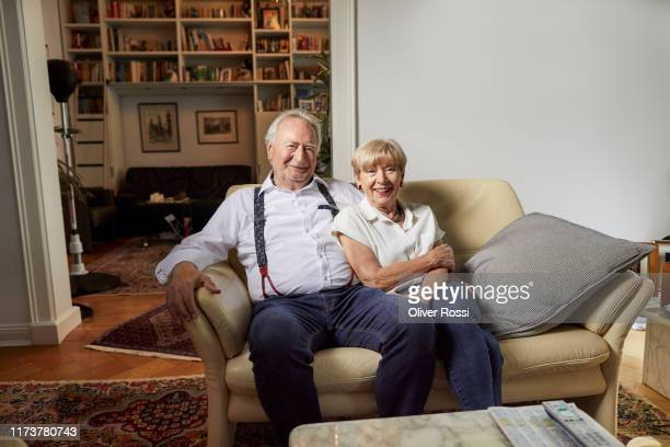 portrait of smiling senior couple sitting on couch at home - wife stock pictures, royalty-free photos & images