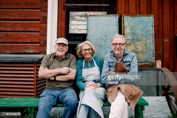 portrait of smiling senior coworkers sitting on bench against hardware store - close to stock pictures, royalty-free photos & images