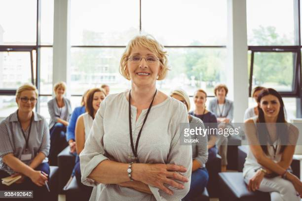 portrait of smiling senior female presenter with audience in background - teacher stock pictures, royalty-free photos & images
