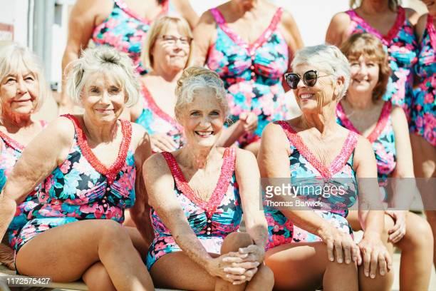 portrait of smiling senior female synchronized swim team - mani incrociate foto e immagini stock