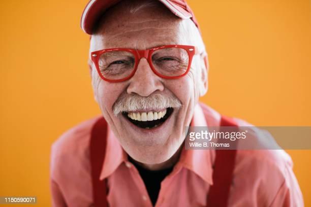 portrait of smiling senior gay man - gay seniors photos et images de collection