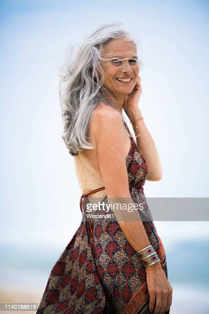 portrait of smiling senior hippie woman with sandy back on the beach - grey dress stock pictures, royalty-free photos & images