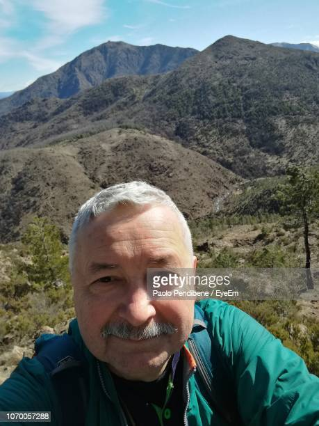 portrait of smiling senior man against mountains - zuid europese etniciteit stockfoto's en -beelden