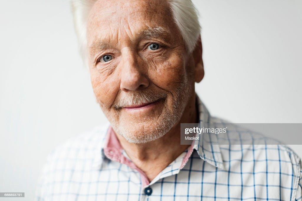 Portrait of smiling senior man against white background : Stock Photo