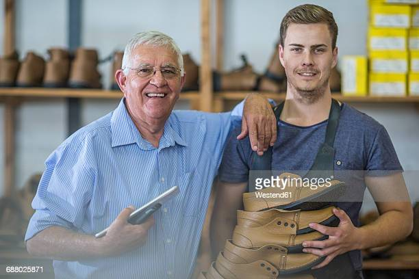 Portrait of smiling senior man and young man holding shoes