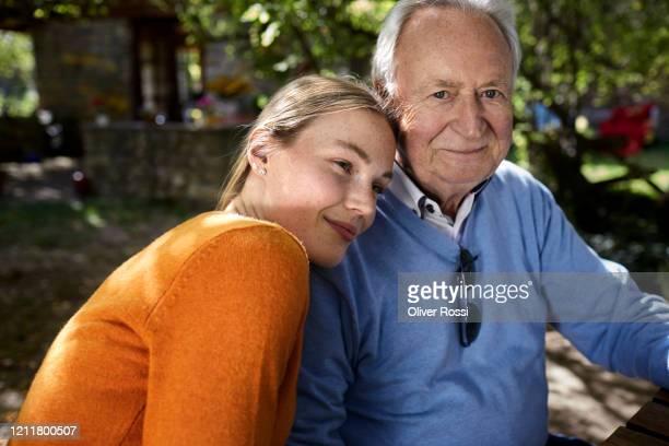 portrait of smiling senior man and young woman in garden - tochter stock-fotos und bilder