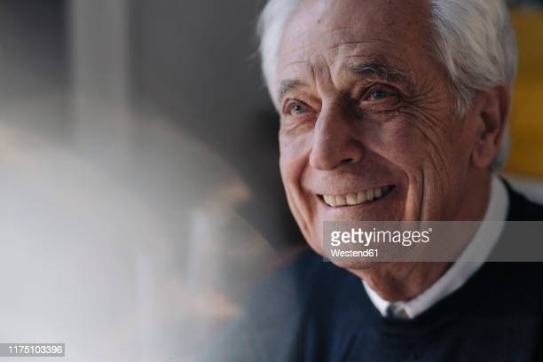 portrait of smiling senior man at home - senior men stock pictures, royalty-free photos & images