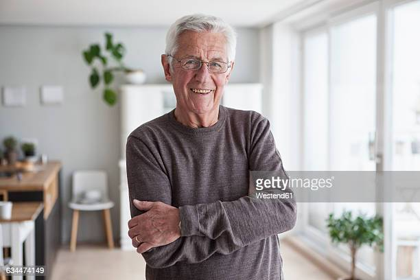 portrait of smiling senior man at home - waist up stock pictures, royalty-free photos & images