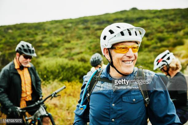 portrait of smiling senior man hanging out with friends before early morning mountain bike ride - cycling stock pictures, royalty-free photos & images