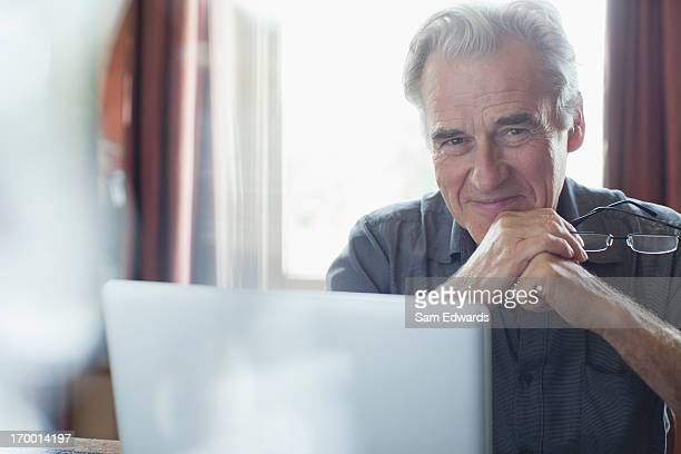 Portrait of smiling senior man holding eyeglasses and using laptop