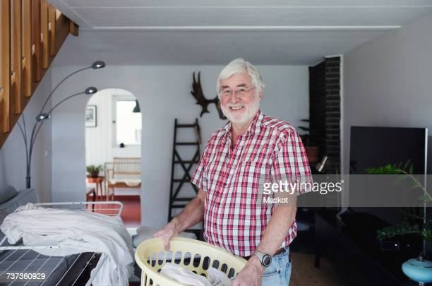 Portrait of smiling senior man holding laundry basket while standing in living room