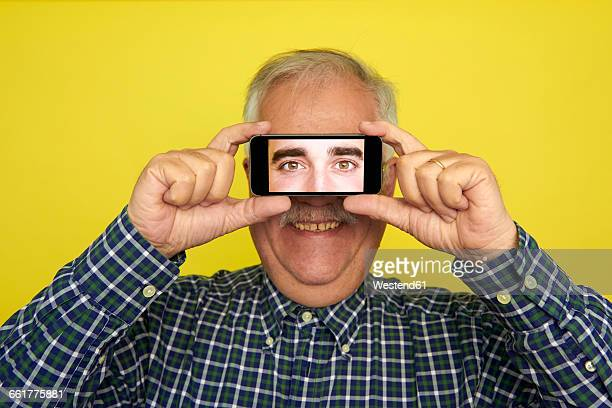 Portrait of smiling senior man holding smartphone with photography of another mans eyes