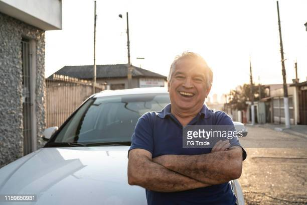 portrait of smiling senior man in front of a car and looking at camera - taxi driver stock pictures, royalty-free photos & images