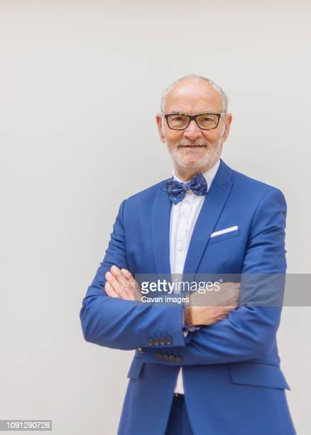 portrait of smiling senior man in suit with arms crossed standing against white background - bow tie stock pictures, royalty-free photos & images