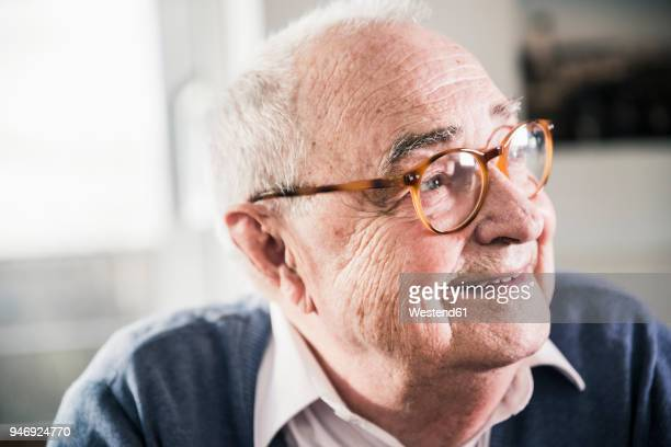 portrait of smiling senior man looking sideways - senior stock-fotos und bilder