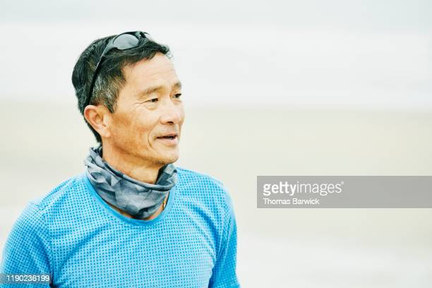 portrait of smiling senior man on beach during early morning workout - 襟元の服飾品 ストックフォトと画像