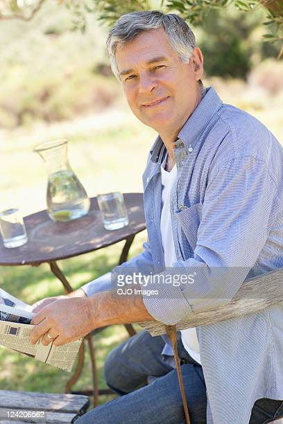 Portrait of smiling senior man reading newspaper in chair at the lawn