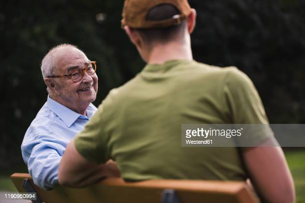 portrait of smiling senior man relaxing together with his grandson on a park bench - doing a favor stock pictures, royalty-free photos & images