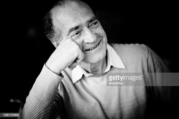 portrait of smiling senior man resting head on hand - fine art portrait stock photos and pictures