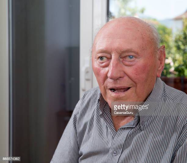 Portrait Of Smiling Senior Man Sitting In His Bedroom At The Nursing Home
