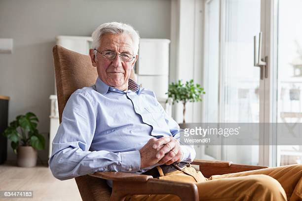 portrait of smiling senior man sitting on armchair at home - one senior man only stock pictures, royalty-free photos & images