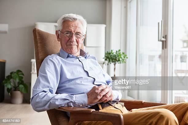 portrait of smiling senior man sitting on armchair at home - armstoel stockfoto's en -beelden