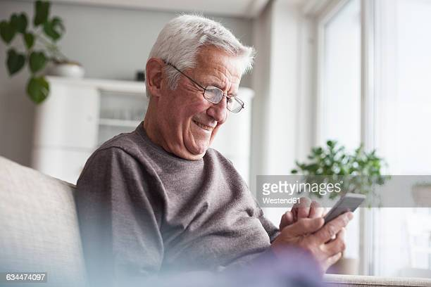 Portrait of smiling senior man sitting on couch at home using smartphone