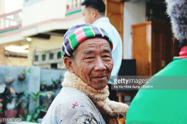 portrait of smiling senior man sitting outdoors - ko ko htike aung stock pictures, royalty-free photos & images