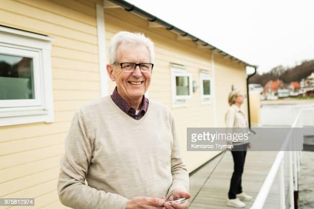 Portrait of smiling senior man standing on pier