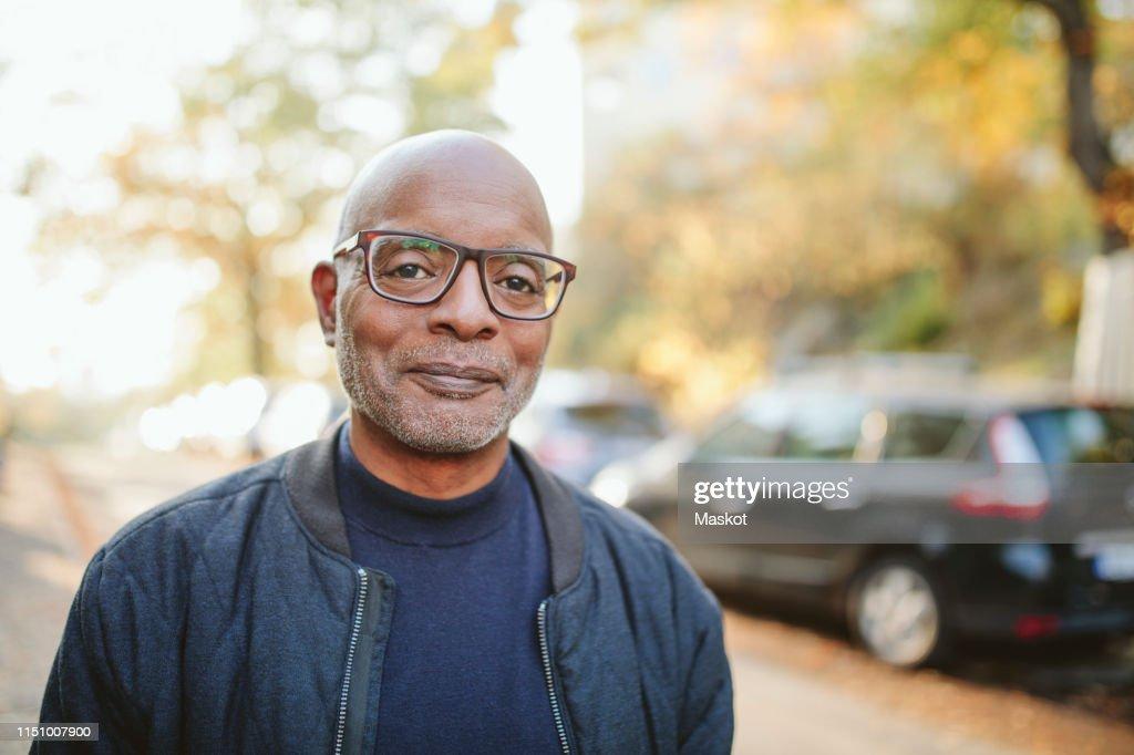 Portrait of smiling senior man standing on road : Stockfoto