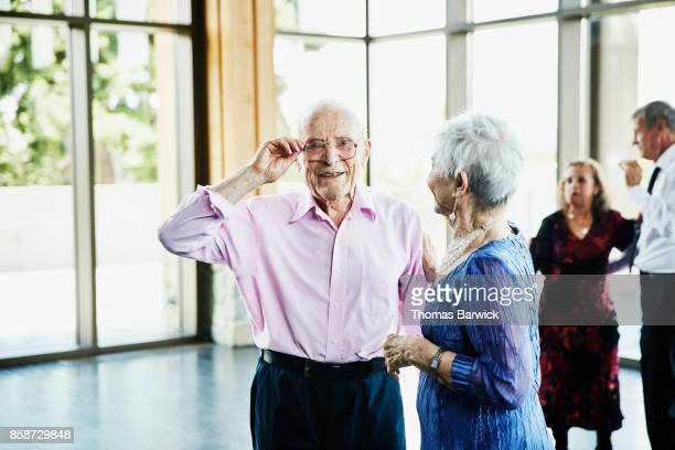 Portrait of smiling senior man standing with partner after dancing in ballroom