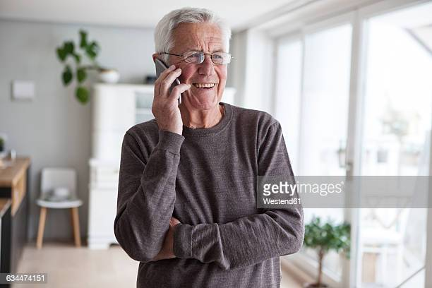 Portrait of smiling senior man telephoning with smartphone at home