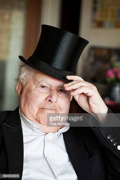 Portrait of smiling senior man tipping top hat