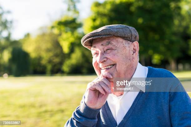 portrait of smiling senior man wearing cap - senior stock-fotos und bilder