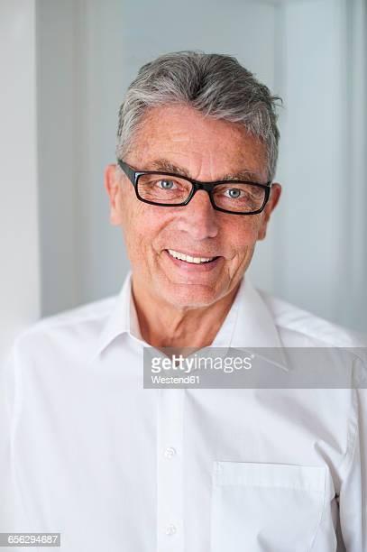Portrait of smiling senior man wearing glasses and white shirt