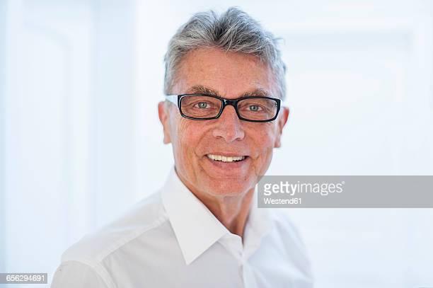 portrait of smiling senior man wearing glasses and white shirt - wit hemd stockfoto's en -beelden