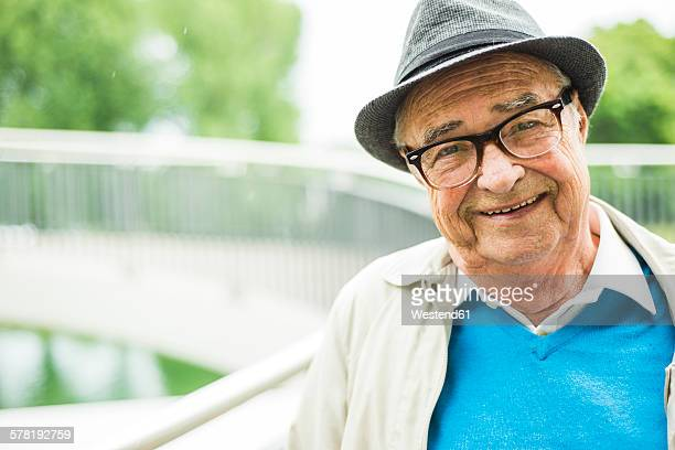 Portrait of smiling senior man wearing glasses ans and hat