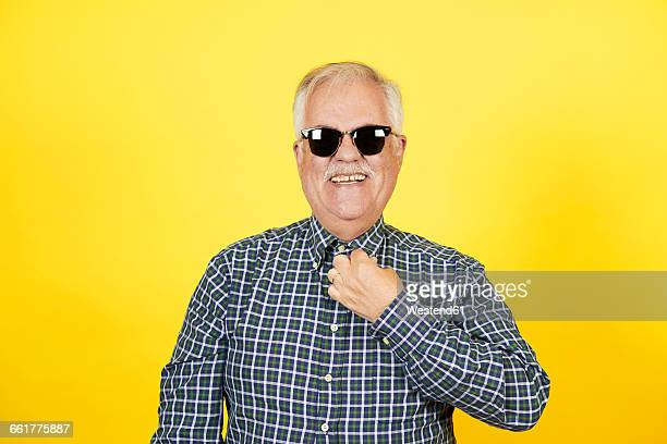 Portrait of smiling senior man wearing sunglasses in front of yellow background
