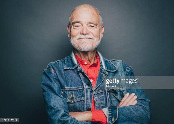 portrait of smiling senior man with arms crossed against gray background - einzelner senior stock-fotos und bilder