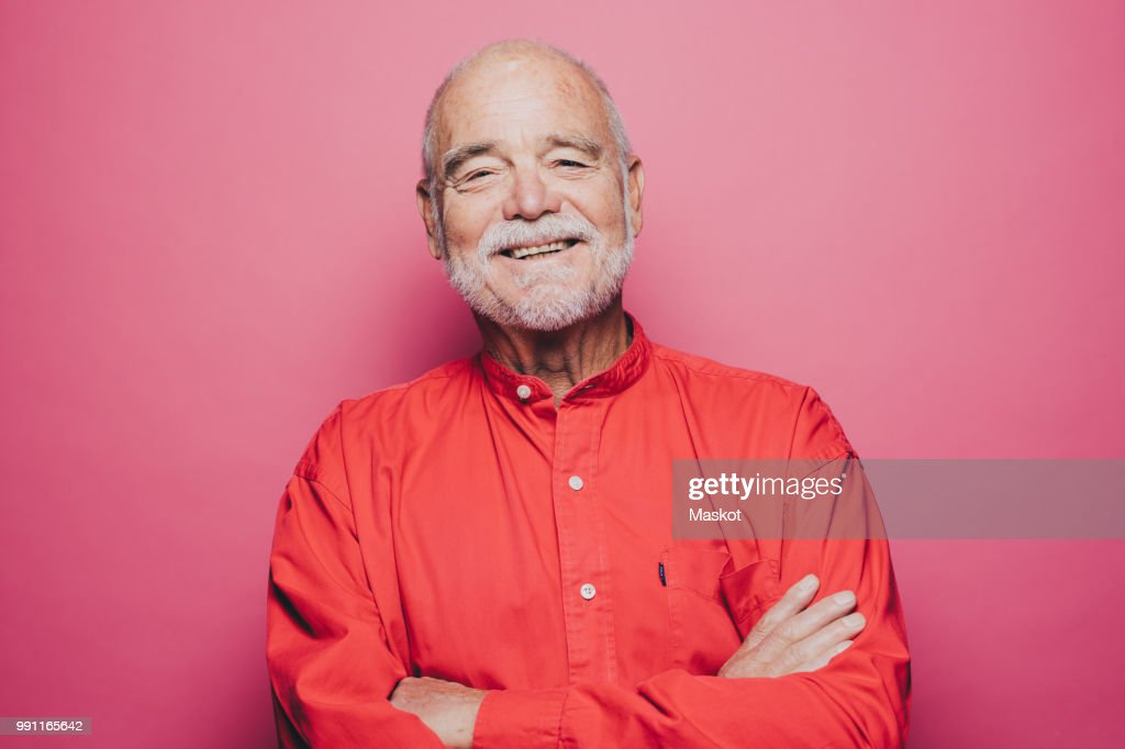 Portrait of smiling senior man with arms crossed against pink background : Stock Photo