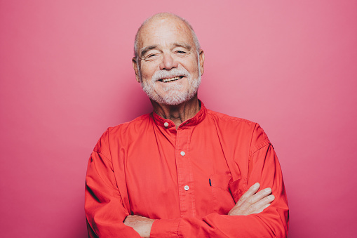 Portrait of smiling senior man with arms crossed against pink background - gettyimageskorea