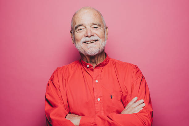 portrait of smiling senior man with arms crossed against pink background - 彩色影像 個照片及圖片檔