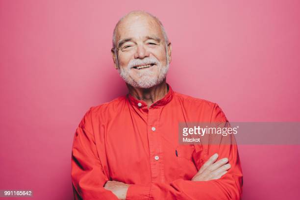 portrait of smiling senior man with arms crossed against pink background - enthousiaste photos et images de collection