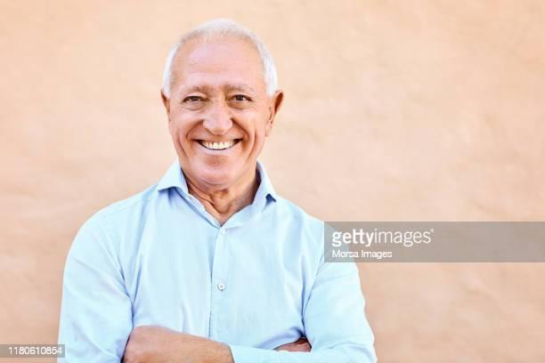 retrato de un hombre mayor sonriente con los brazos cruzados - un solo hombre fotografías e imágenes de stock