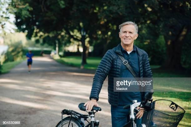 portrait of smiling senior man with bicycle standing in park - 65 69 jaar stockfoto's en -beelden