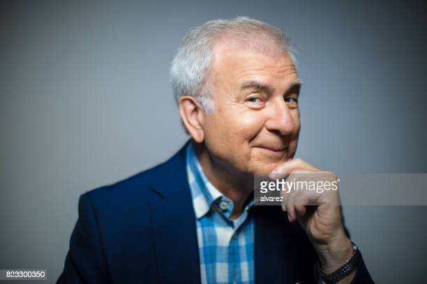 Portrait Of Smiling Senior Mann mit Hand am Kinn