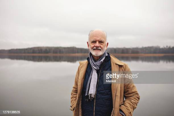 portrait of smiling senior man with hands in pockets standing against lake - lake stock pictures, royalty-free photos & images
