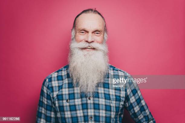 ae3e4b958 Portrait of smiling senior man with long white beard against pink background
